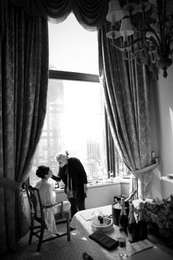 Bride getting her make up applied in front of a large window at a hotel