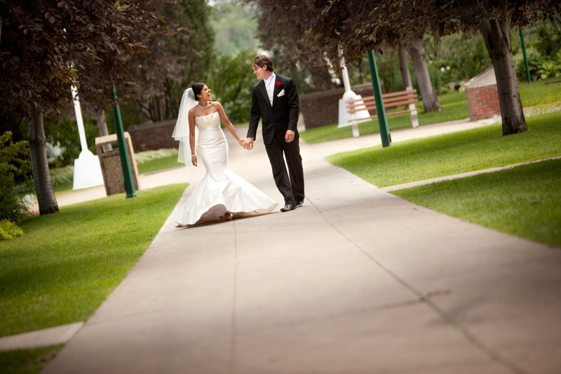 Bride and groom holding hands looking at each other walking on a pathway at the Alberta Legislative