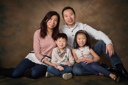 Family of four sitting together in front of a brown studio background