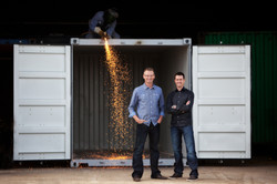 Two men standing in front of an open container unit that is being welded