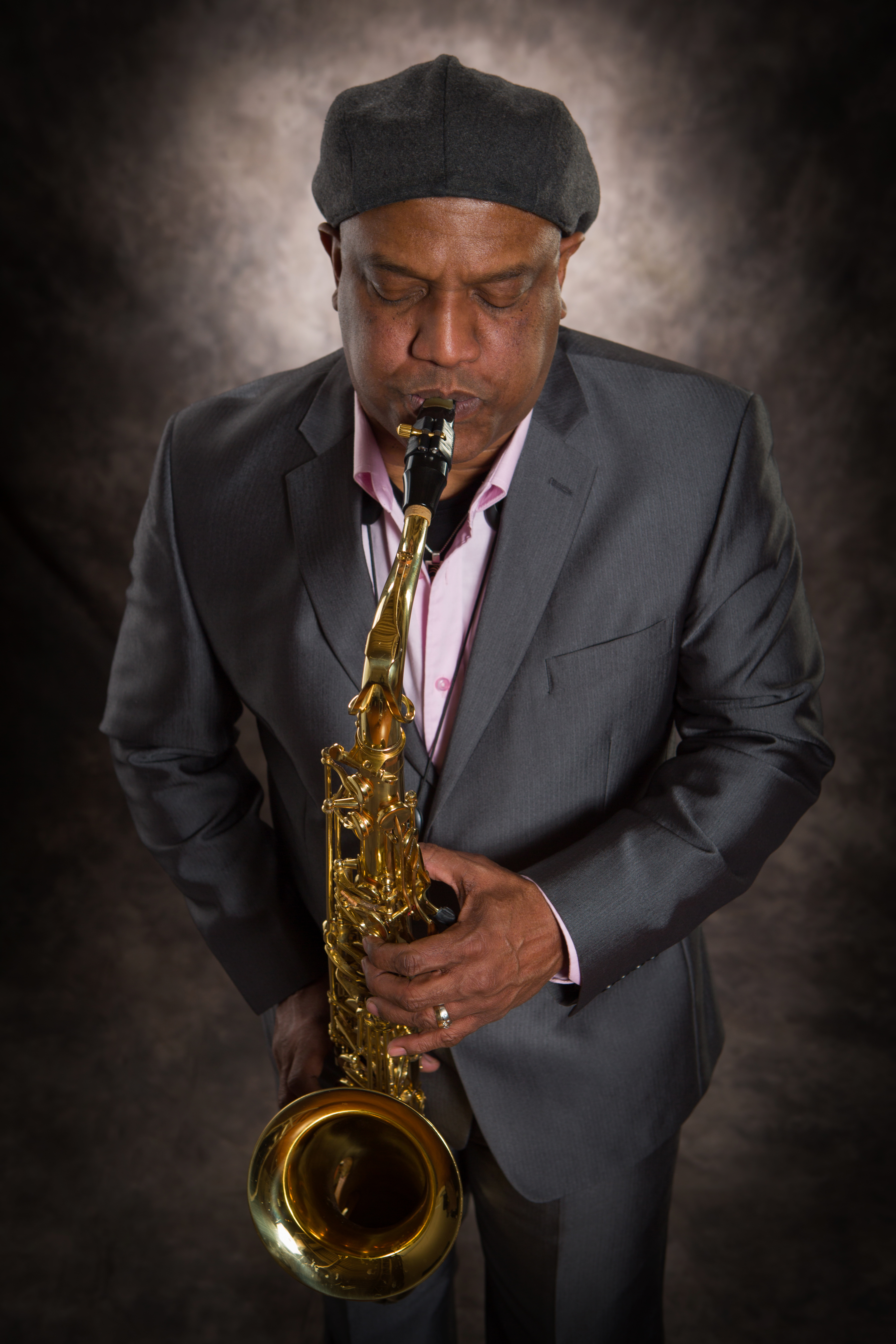 Man wearing a grey hat and suit playing the saxophone