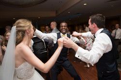 Bride and groom dancing with smiling guest