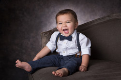 Toddler boy dressed in a dress shirt, suspenders and bowtie sitting on a couch smiling
