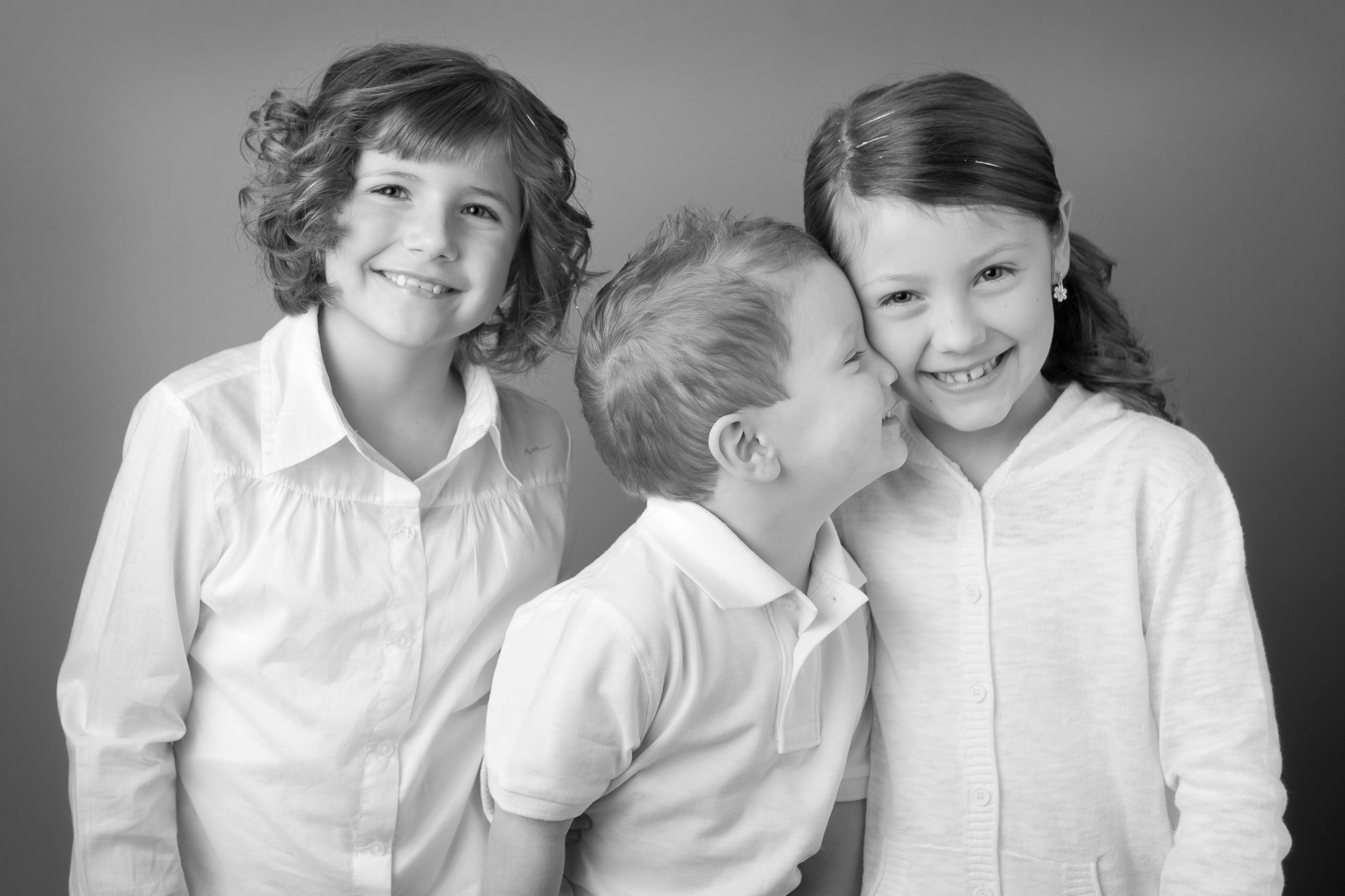 Three young children in white shirts pose together playfully