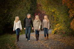 Family of four walking on a pathway in a park