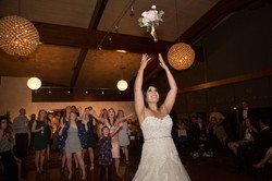 Bride tossing her bouquet over her shoulders into crowd of females eagerly trying to catch it