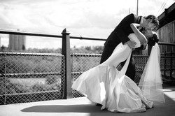 Groom holding his bride as he dips her for a kiss on a bridge