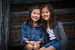 Two young sisters with big smiles dressed in denim sitting side by side