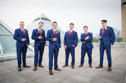 Groom and groomsmen pose with cigars with the Muttart Conservatory pyramids in the background