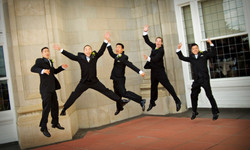 Groom and groomsmen jumping in the air with fun expressions