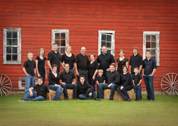 Large extended family posing in front of a red barn
