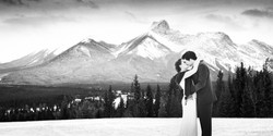 Bride and groom embrace and kiss with mountains in the backgound