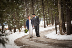 Bride and groom holding hands. walking down road in winter setting