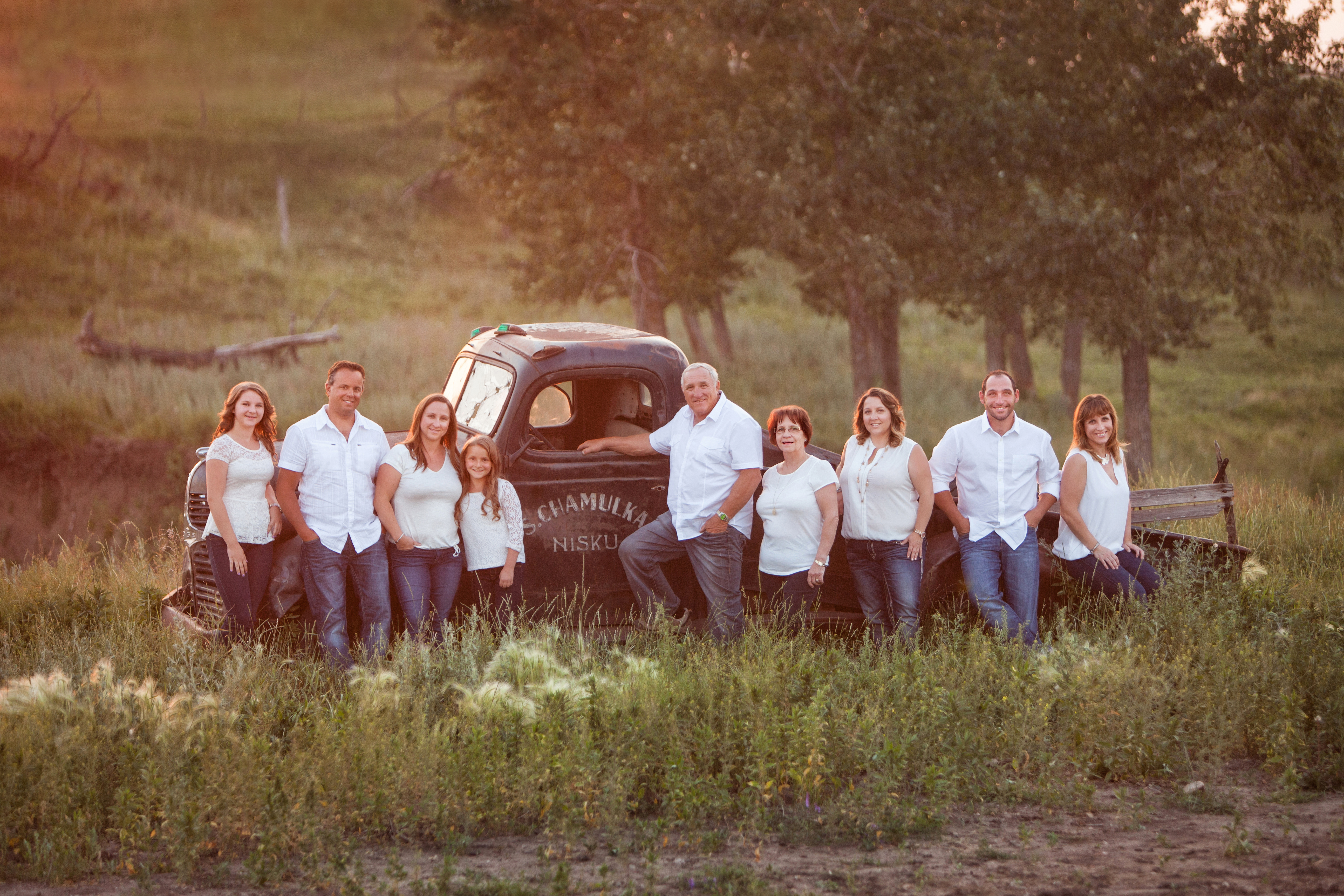Extended family of nine in white tops and jeans standing in front of vintage truck