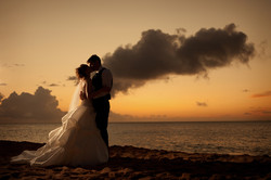 Silhouette of bride and groom kissing on a beach at sunset