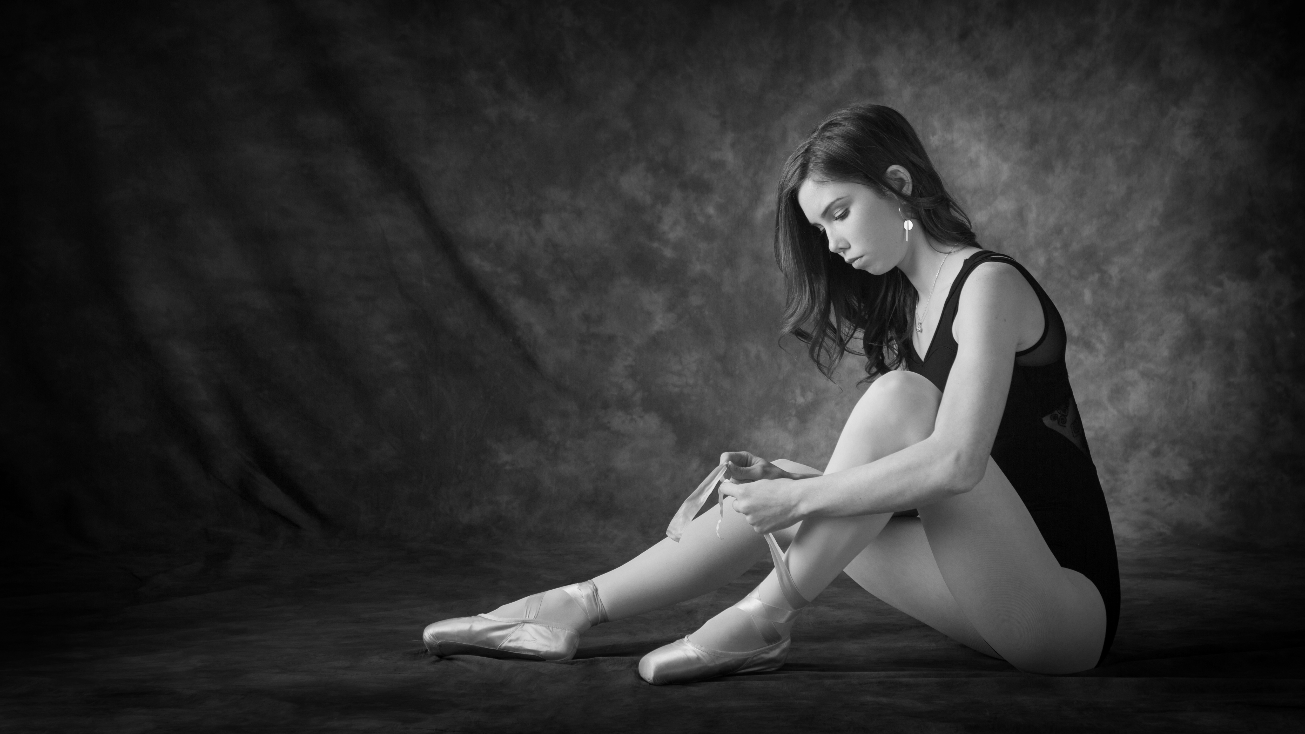 Girl in ballet attire sitting while tying her ballet shoe