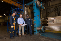Three men standing in an industrial production facility discussing plans