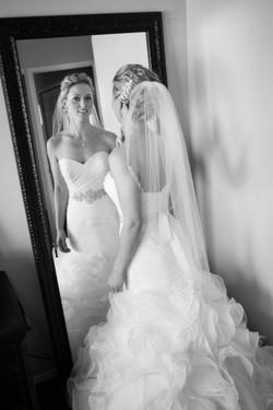 Bride in wedding dress looking into a mirror