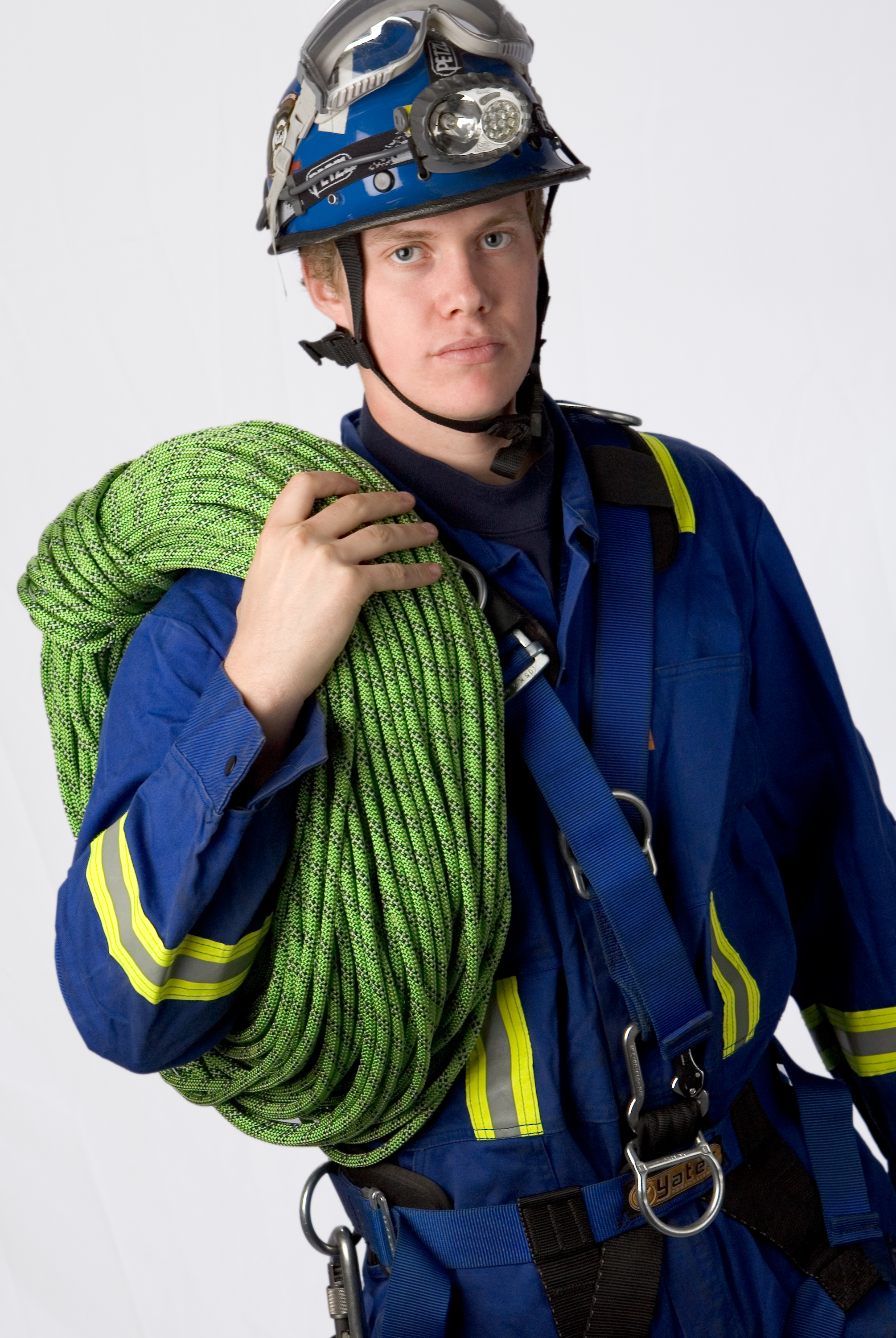 Young man in overalls and hard hat holding safety rope