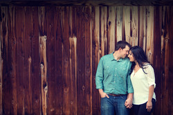 Engaged couple standing together with heads touching in front of rustic wooden building