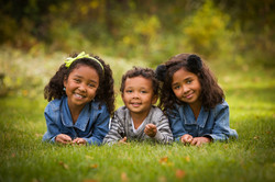 Three young siblings smile at the camera as they lay on the grass