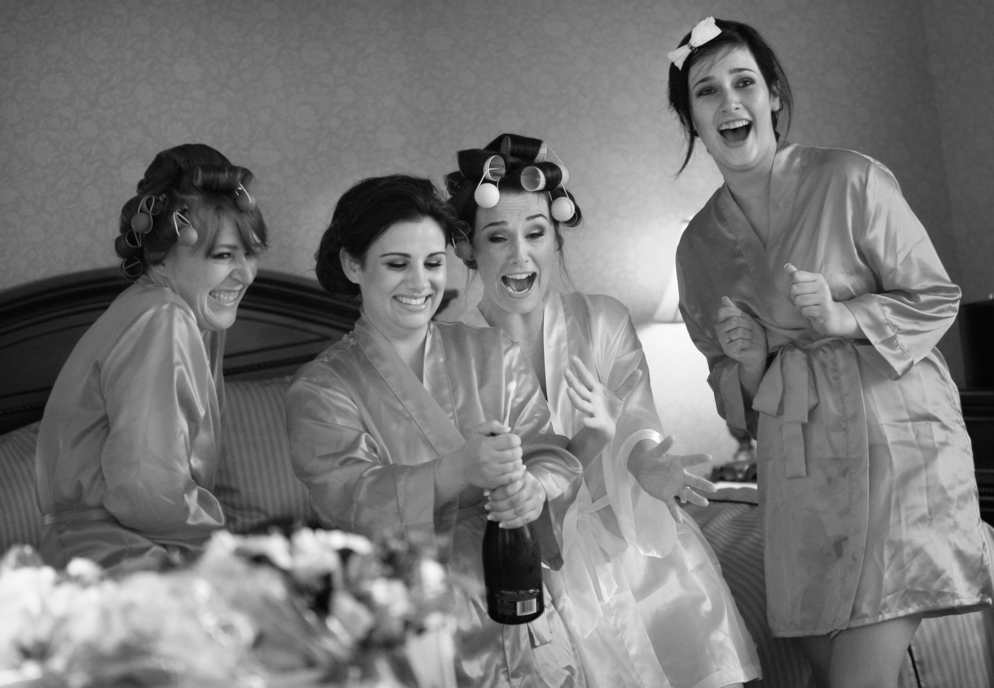 Bridesmaids in robes look on in excitement as one of them pops the cork on a champagne bottle