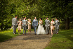 Bridal party walking arm in arm on pathway while smiling and interacting with each other
