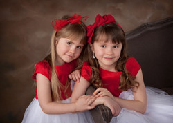 Two young sisters dressed in red dresses and hair bows