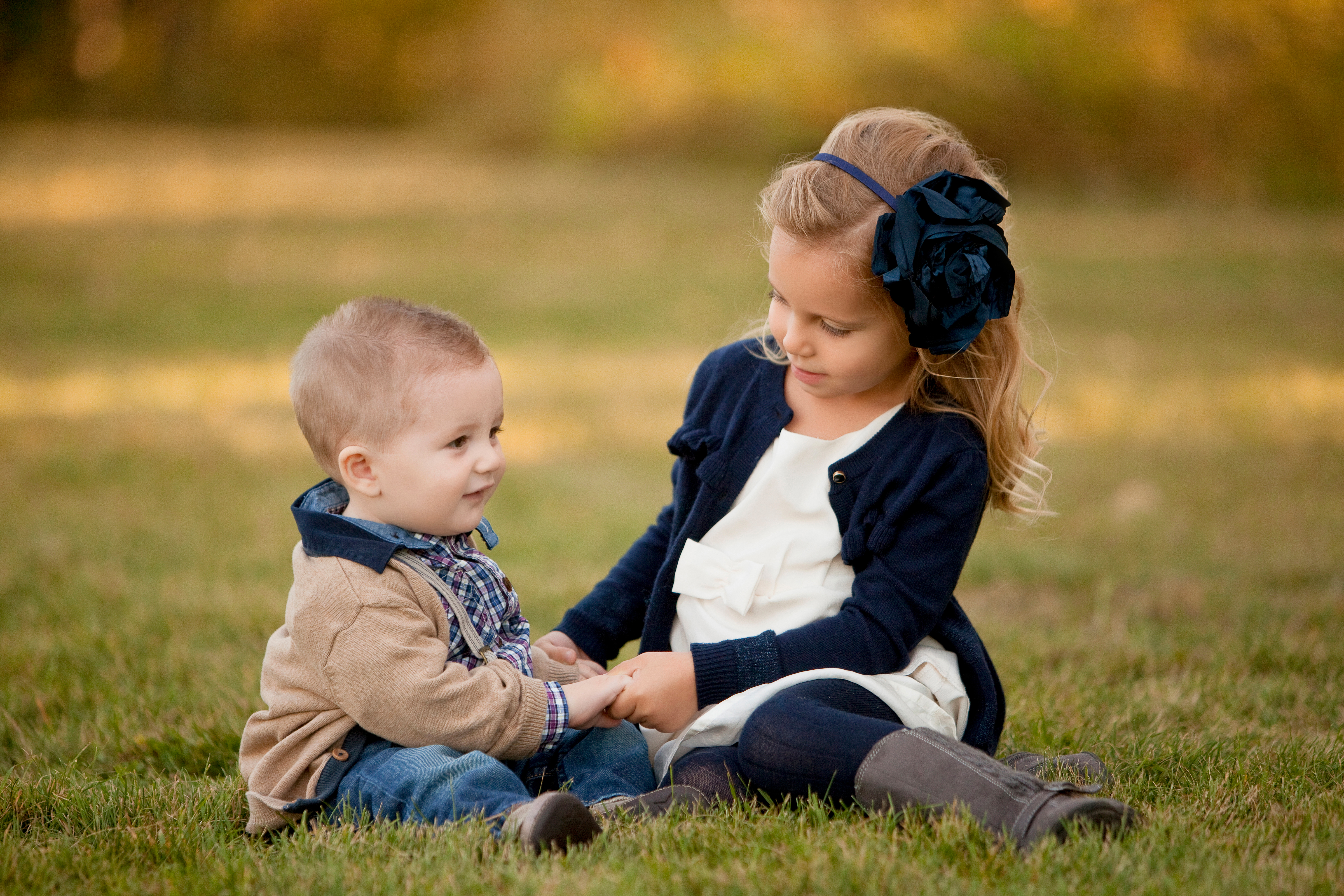 Two nicely dressed young children interact together while sitting on the grass