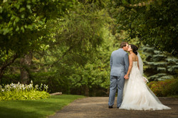 Bride and groom having a kiss on a pathway in garden setting