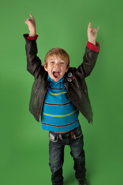 Boy in leather jacket raising his arms with a playful expression