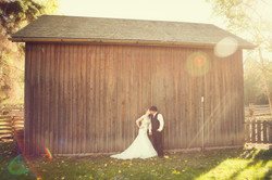 Bride and groom kissing in front of a barn at Fort Edmonton Park