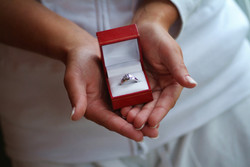 Hands holding red ring box containing diamond engagement ring