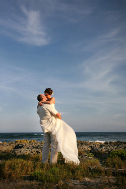 Groom picking up bride as they kiss on a rock beach over looking the ocean