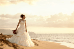 Bride holding bouquet standing on sandy beach in Hawaii looking out into the ocean