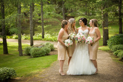 Bride and bridesmaids holding bouquets standing on pathway in park setting looking at each other