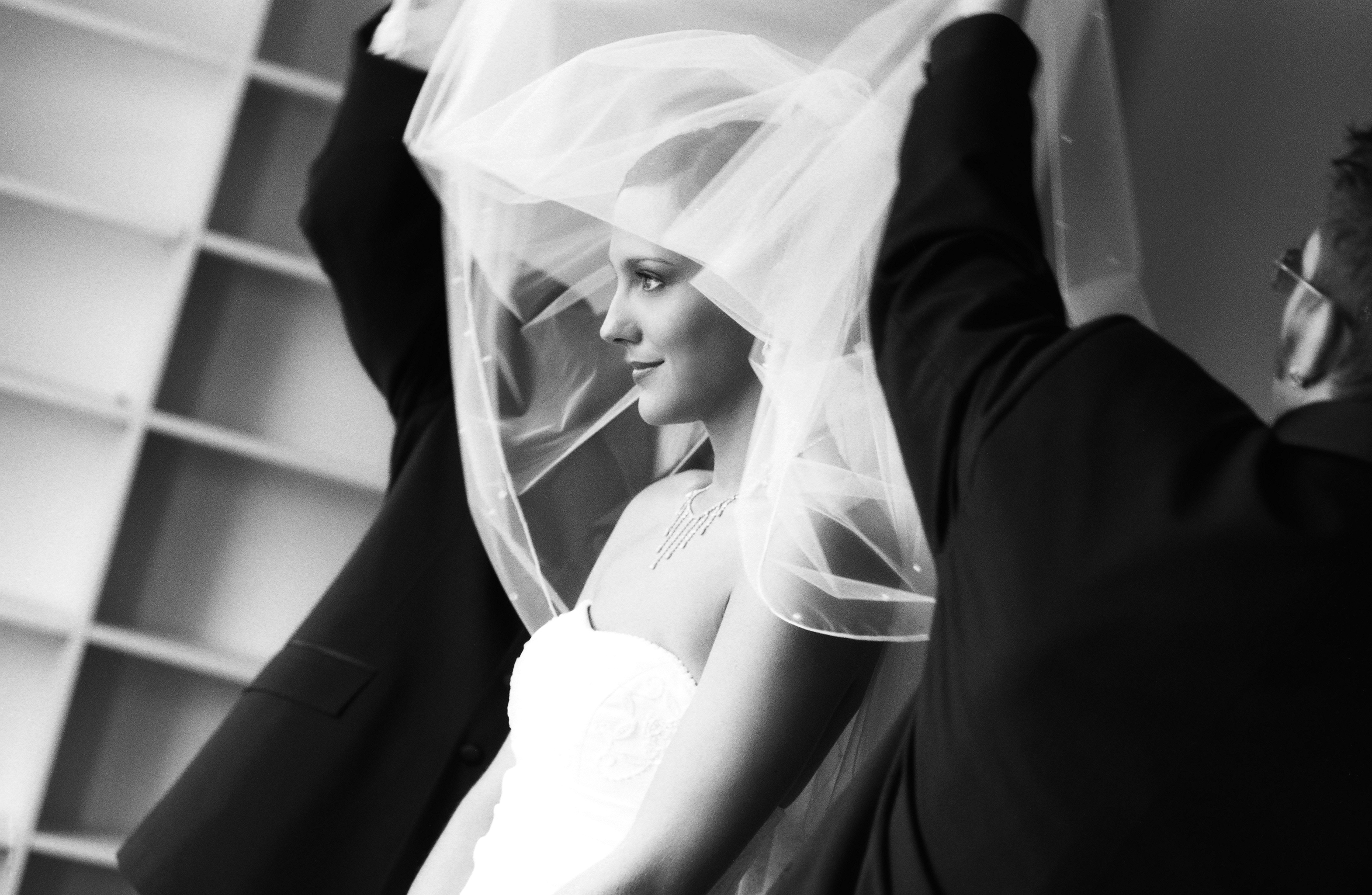 Brides veil being lifted up over her head