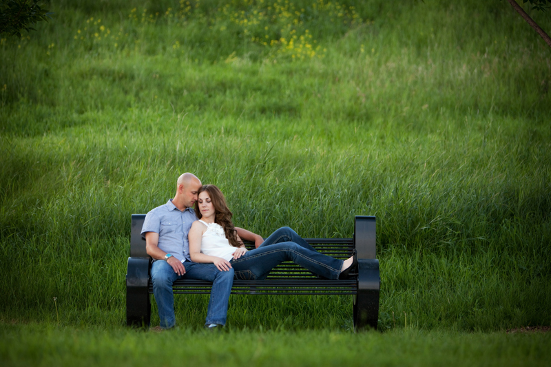 Engaged couple sitting together on a black bench at the park