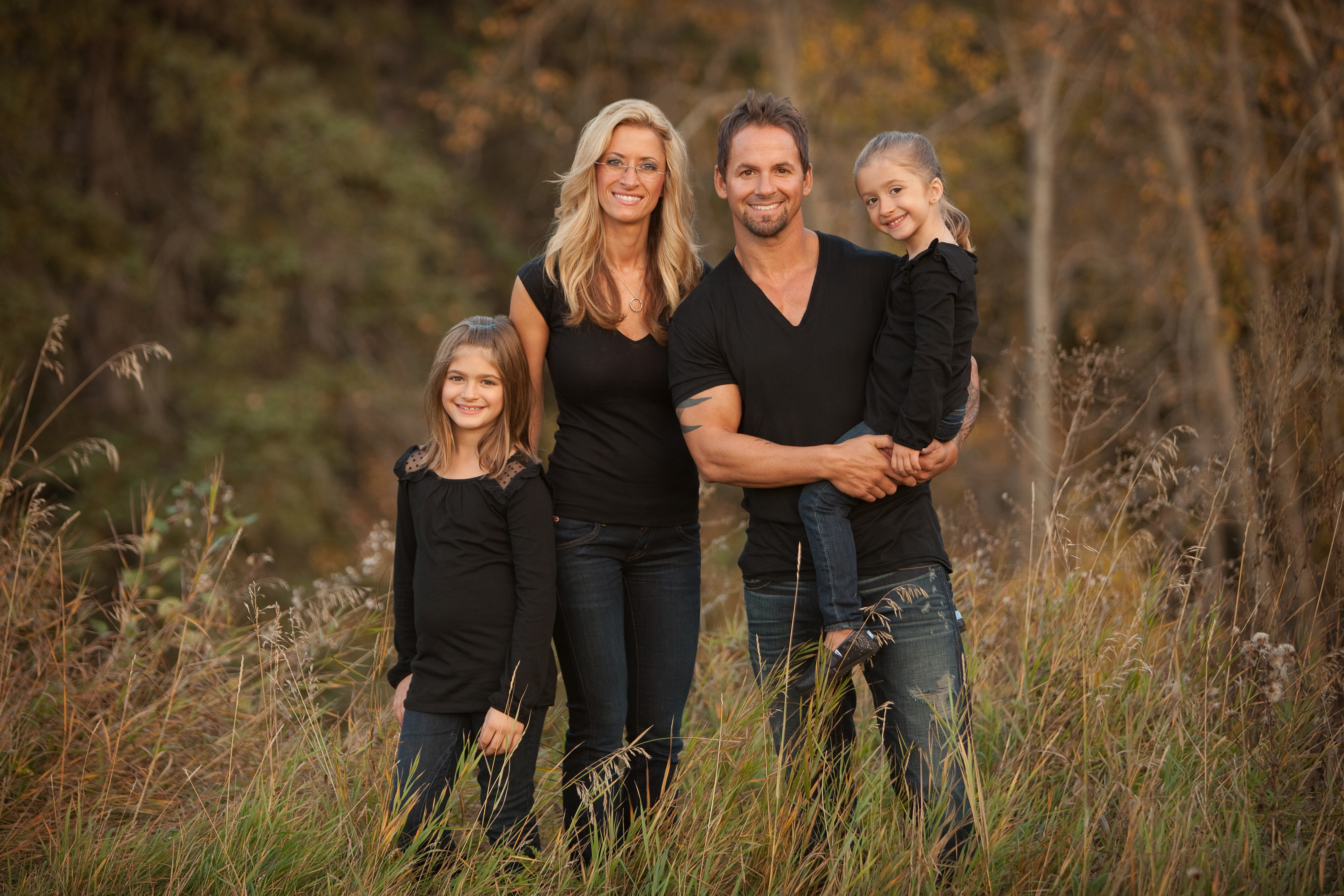 Family of four dressed in black standing together