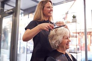 senior-woman-having-hair-cut-by-female-stylist-in-2021-04-05-20-43-57-utc.jpg