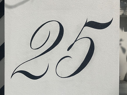 Hand painted 25 house number on column