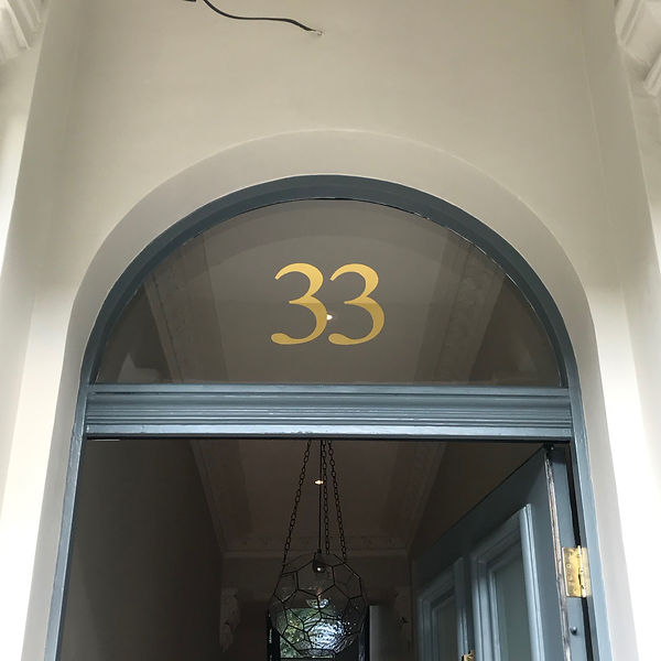 hand painted and gilded 33 house number in gold leaf on transom window above front door