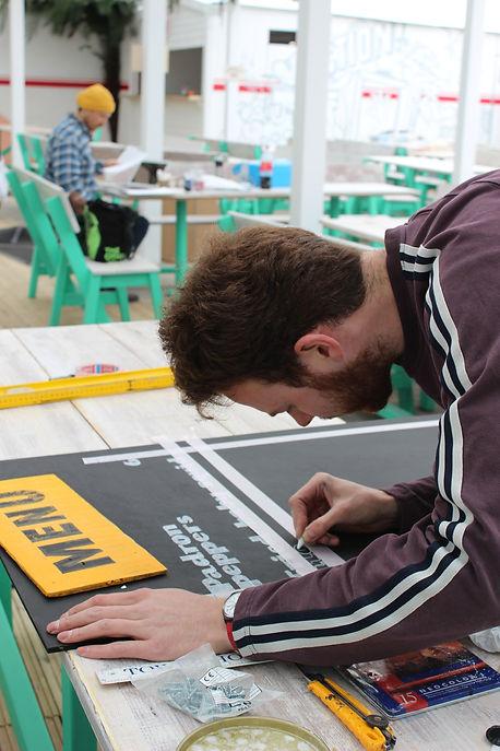 signwriter hand lettering a chalk menu board for restaurant pop up event