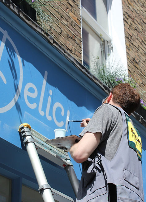 Signwriter painting shop front sign
