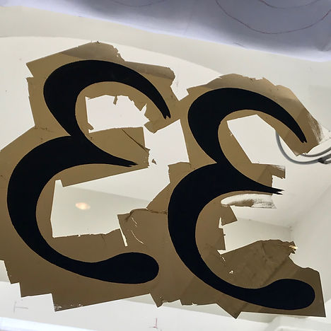 process shot showing applied gold leaf and internal painting to hand painted house number on transom window