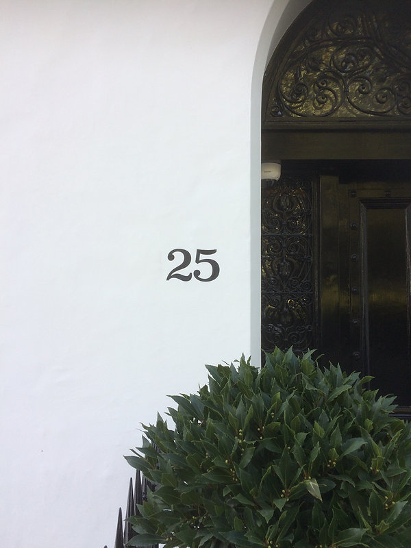 Black hand painted 25 house number by front door