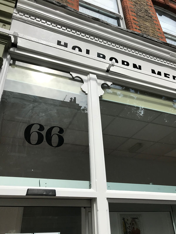 Hand painted 66 building number on shop window