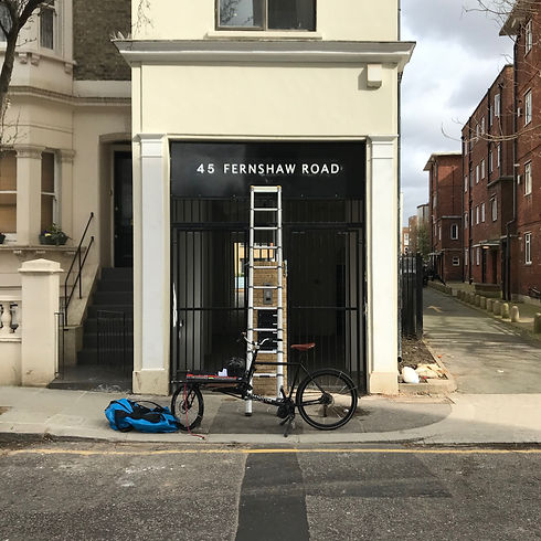 Hand painted building name with signwriter's ladder and bicycle in front