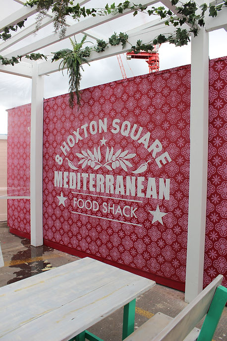 stenciled patterned wall with hand painted signage for restaurant pop up event
