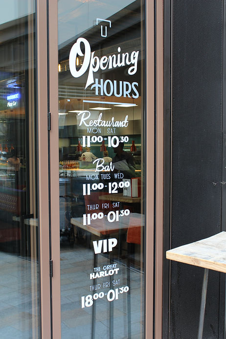 hand painted opening hours for restaurant on glass window panel